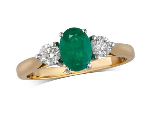 18 carat yellow gold three stone ring, with an oval cut emerald centre weighing 0.67ct, and one brilliant cut diamond on each shoulder. Total diamond weight: 0.32ct.