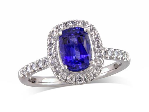 Platinum set cluster ring, with an exceptional blue cushion cut sapphire centre in a claw setting, with a diamond surround and diamond set shoulders. Total cluster diamond weight: 0.41ct.