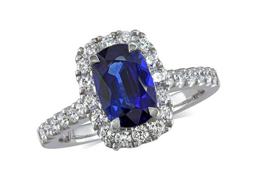 Platinum cluster ring, with a cushion cut sapphire centre in a claw setting, with a surrounding diamond set bezel and diamond shoulders. Total cluster diamond weight: 0.67ct.