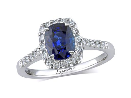 Platinum set cluster ring, with an exceptional blue cushion cut sapphire centre in a claw setting, with a surrounding diamond set bezel and diamond shoulders. Total cluster diamond weight: 0.38ct.