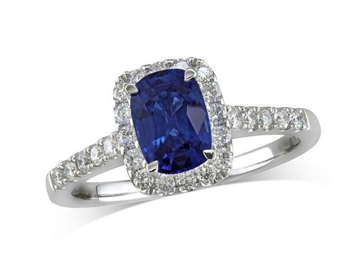Platinum set cluster ring, with an exceptional blue cushion cut sapphire centre in a claw setting, with a surrounding diamond set bezel and diamond shoulders. Total cluster diamond weight: 0.36ct.