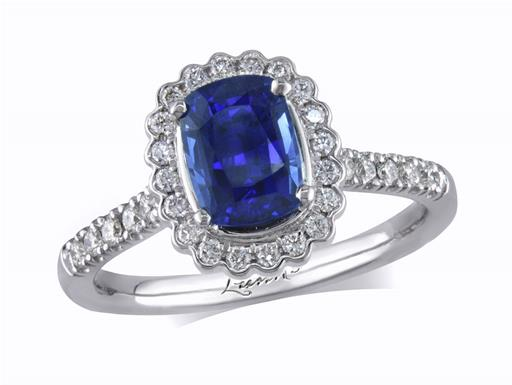 Platinum set cluster ring, with an exceptional blue cushion cut sapphire centre in a claw setting, with a diamond surround and diamond set shoulders. Total cluster diamond weight: 0.34ct.