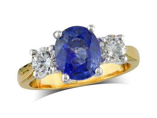 18 carat yellow gold three stone ring, with an oval cut sapphire centre weighing 2.43ct, and one brilliant cut diamond on each shoulder. Total diamond weight: 0.68ct.