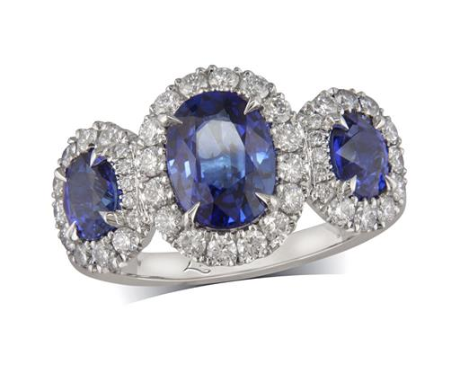 Platinum three stone ring, with three oval cut sapphires, each in a four claw setting, with a surrounding diamond set bezel. Total diamond weight: 0.57ct.