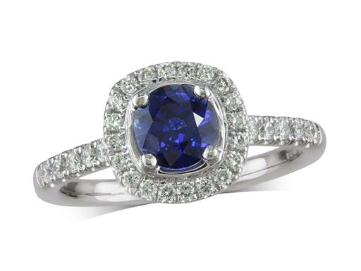 Platinum cluster ring, with a brilliant cut sapphire centre in a four claw setting, with a surrounding diamond set bezel and diamond shoulders. Total cluster diamond weight: 0.34ct.