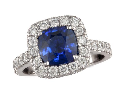 Platinum cluster ring, with a cushion cut sapphire centre in a claw setting, with a surrounding diamond set bezel and diamond shoulders. Total cluster diamond weight: 0.80ct.