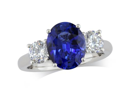 Platinum ring, with an oval cut sapphire centre weighing 1.96ct in a four claw setting, and one brilliant cut diamond on each shoulder. Total diamond weight: 0.72ct.