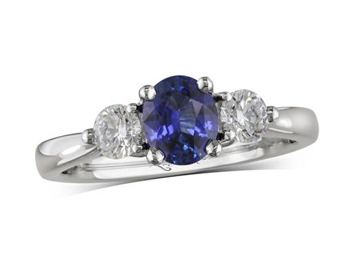 Platinum three stone ring, with an oval cut sapphire centre weighing 0.79ct, and one brilliant cut diamond on each shoulder. Total diamond weight: 0.41ct.
