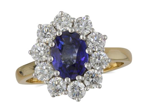 18 carat yellow gold cluster ring, with an oval cut Sapphire centre weighing 1.41ct in a claw setting, with 10 brilliant cut diamonds surrounding. Total cluster diamond weight: 1.17ct.