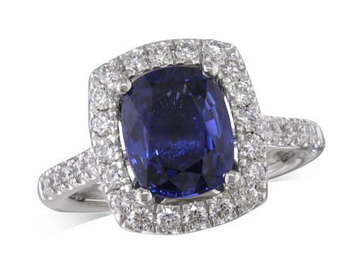 Platinum cluster ring, with a cushion cut sapphire centre in a claw setting, with a surrounding diamond set bezel and diamond shoulders. Total cluster diamond weight: 0.68ct.
