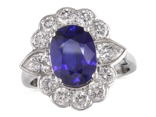 Platinum cluster ring, with an oval cut sapphire centre weighing 2.63ct, surrounded by 10 brilliant cut diamonds and 2 pear cut diamonds highlighting the shoulders. Total cluster diamond weight: 1.22ct.