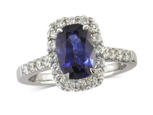Platinum cluster ring, with a cushion cut sapphire centre in a claw setting, with a surrounding diamond set bezel and diamond shoulders. Total cluster diamond weight: 0.65ct.