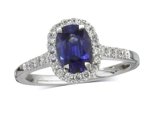 Platinum cluster ring, with a cushion cut sapphire centre in a claw setting, with a surrounding diamond set bezel and diamond shoulders. Total cluster diamond weight: 0.30ct.