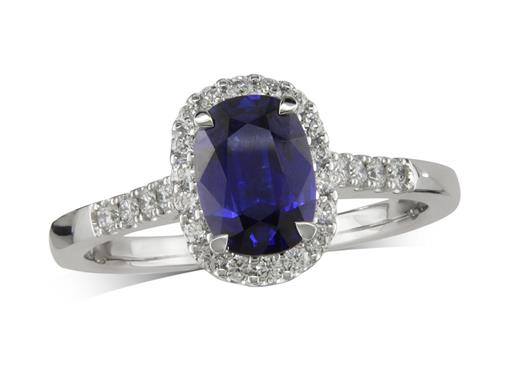Platinum cluster ring, with a cushion cut sapphire centre in a claw setting, with a surrounding diamond set bezel and diamond shoulders. Total cluster diamond weight: 0.28ct.