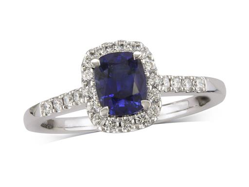 Platinum cluster ring, with a cushion cut sapphire centre in a claw setting, with a surrounding diamond set bezel and diamond shoulders. Total cluster diamond weight: 0.27ct.