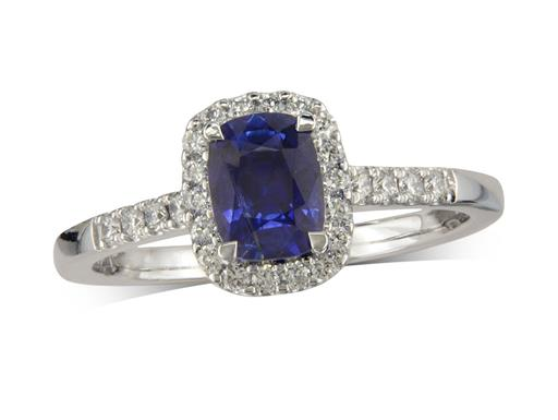 Platinum cluster ring, with a cushion cut sapphire centre in a claw setting, with a surrounding diamond set bezel and diamond shoulders. Total cluster diamond weight: 0.26ct.