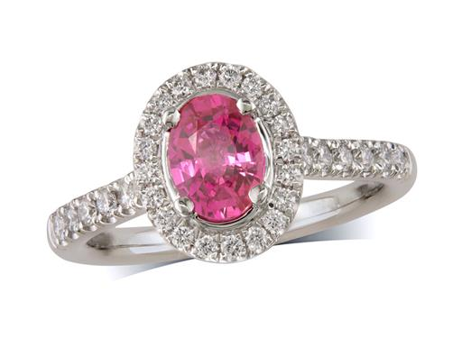 Platinum ring, with an oval cut ruby centre weighing 1.00ct, with a surrounding diamond set bezel and diamond set shoulders. Total diamond weight is 0.39ct.