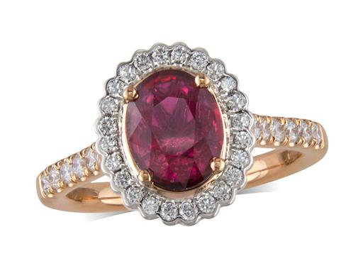 18 carat rose gold ring, with a certificated oval cut ruby centre weighing 1.67ct, with a surrounding diamond set bezel and diamond set shoulders. Total diamond weight is 0.43ct.