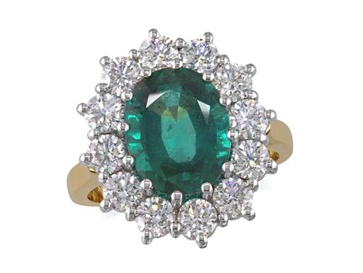 18 carat yellow gold cluster ring, with an oval cut emerald centre weighing 2.97ct, with 12 diamonds surrounding. Total cluster diamond weight: 1.78ct.