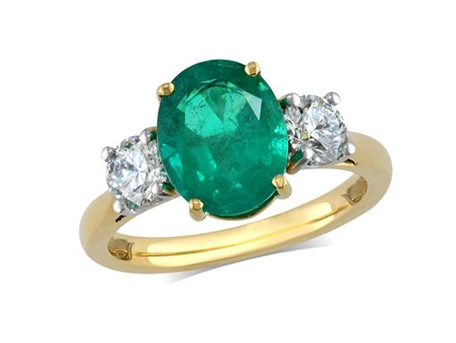 18 carat yellow gold three stone ring, with an oval cut emerald centre weighing 2.13ct, and one brilliant cut diamond on each shoulder. Total diamond weight: 0.72ct.