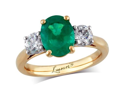 18 carat yellow gold three stone ring, with an oval cut emerald centre weighing 1.56ct, and one brilliant cut diamond on each shoulder. Total diamond weight: 0.66ct.