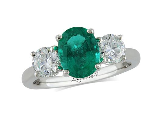 Platinum three stone ring, with an oval cut emerald centre weighing 1.75ct, and one brilliant cut diamond on each shoulder. Diamonds certificated as weighing 1.00ct total, colour E and clarity SI1.
