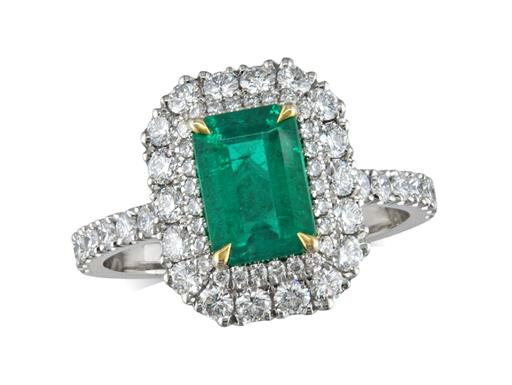 This stunning platinum, emerald and diamond ring has a centre step cut emerald weighing 1.05ct complimented by yellow gold claws and surrounded by a double row of brilliant cut diamonds and diamond set shoulders. Total diamond weight 0.80ct.