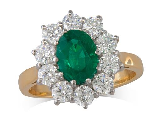 18 carat yellow gold cluster ring, with an oval cut emerald centre weighing 1.24ct, surrounded by 10 brilliant cut diamonds. Total cluster diamond weight: 1.18ct.