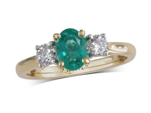 18 carat yellow gold three stone ring, with an oval cut emerald centre weighing 0.70ct, and one brilliant cut diamond on each shoulder. Total diamond weight: 0.35ct.