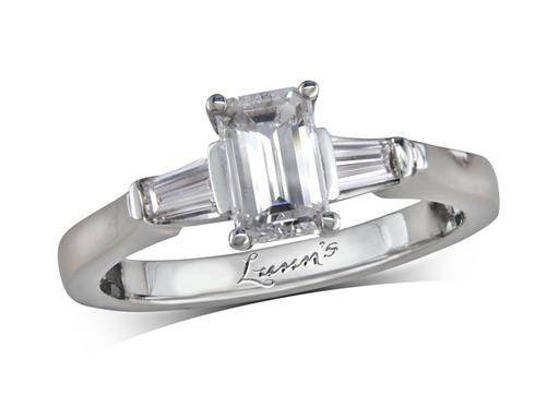 Platinum single stone diamond engagement ring, with a certificated emerald cut centre in a four claw setting, and one taper cut on each shoulder. Total diamond weight: 0.99ct.