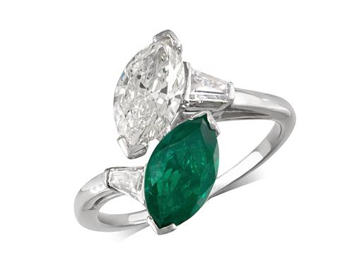 Pre-owned twist style ring, tested as platinum, with a certificated marquise cut diamond weighing 0.92ct, colour G and clarity I1, and a certificated marquise cut emerald weighing 0.89ct.
