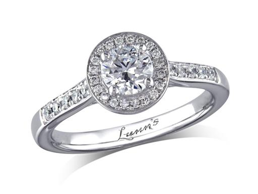 Platinum set diamond cluster engagement ring, with a certificated brilliant cut centre in a four claw setting, with a surrounding diamond set bezel and diamond set shoulders. Perfect fit with a wedding ring. Total cluster diamond weight: 0.72ct.