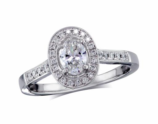 Platinum set diamond cluster engagement ring, with a certificated oval cut centre in a four claw setting, with a surrounding diamond set bezel and diamond set shoulders. Perfect fit with a wedding ring. Total cluster diamond weight: 0.67ct.