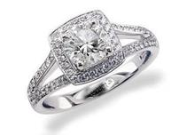 Platinum set diamond engagement ring, with a certificated brilliant cut in a four claw setting, surrounded by a diamond set cluster and split shoulders. Perfect fit with a wedding ring. Total diamond weight: 1.15ct.