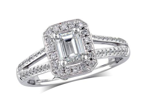Platinum set diamond engagement ring, with a certificated emerald cut in a four claw setting, surrounded by a diamond set cluster and split shoulders. Perfect fit with a wedding ring. Total diamond weight: 0.74ct.