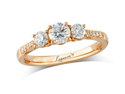 18 carat rose gold set three stone diamond engagement ring, with a certificated brilliant cut centre in a four claw setting, and one brilliant cut on each side with diamond set shoulders. Perfect fit with a wedding ring. Total diamond weight: 0.67ct.