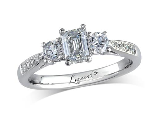 Platinum three stone diamond engagement ring, with a certificated emerald cut centre in a four claw setting, and one brilliant cut on each side with diamond set shoulders. Perfect fit with a wedding ring. Total diamond weight: 0.88ct