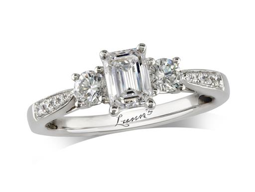 Platinum three stone diamond engagement ring, with a certificated emerald cut centre in a four claw setting, and one brilliant cut on each side with diamond set shoulders. Perfect fit with a wedding ring. Total diamond weight: 0.97ct.
